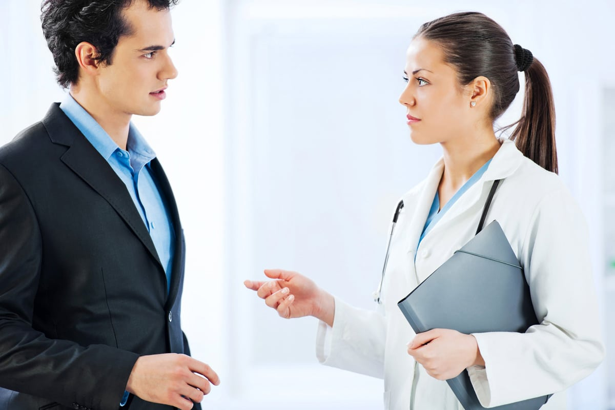 Sales rep with a veterinarian representative of acknowledging what he hears.