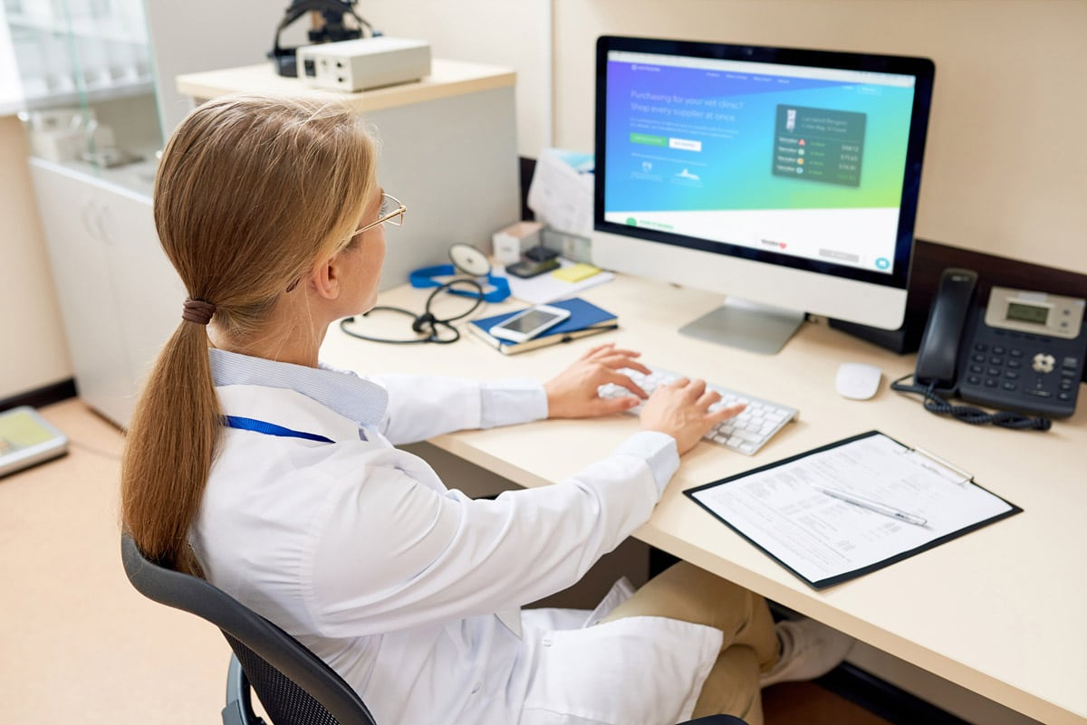 Photo of veterinarian at her computer using Vetcove software.
