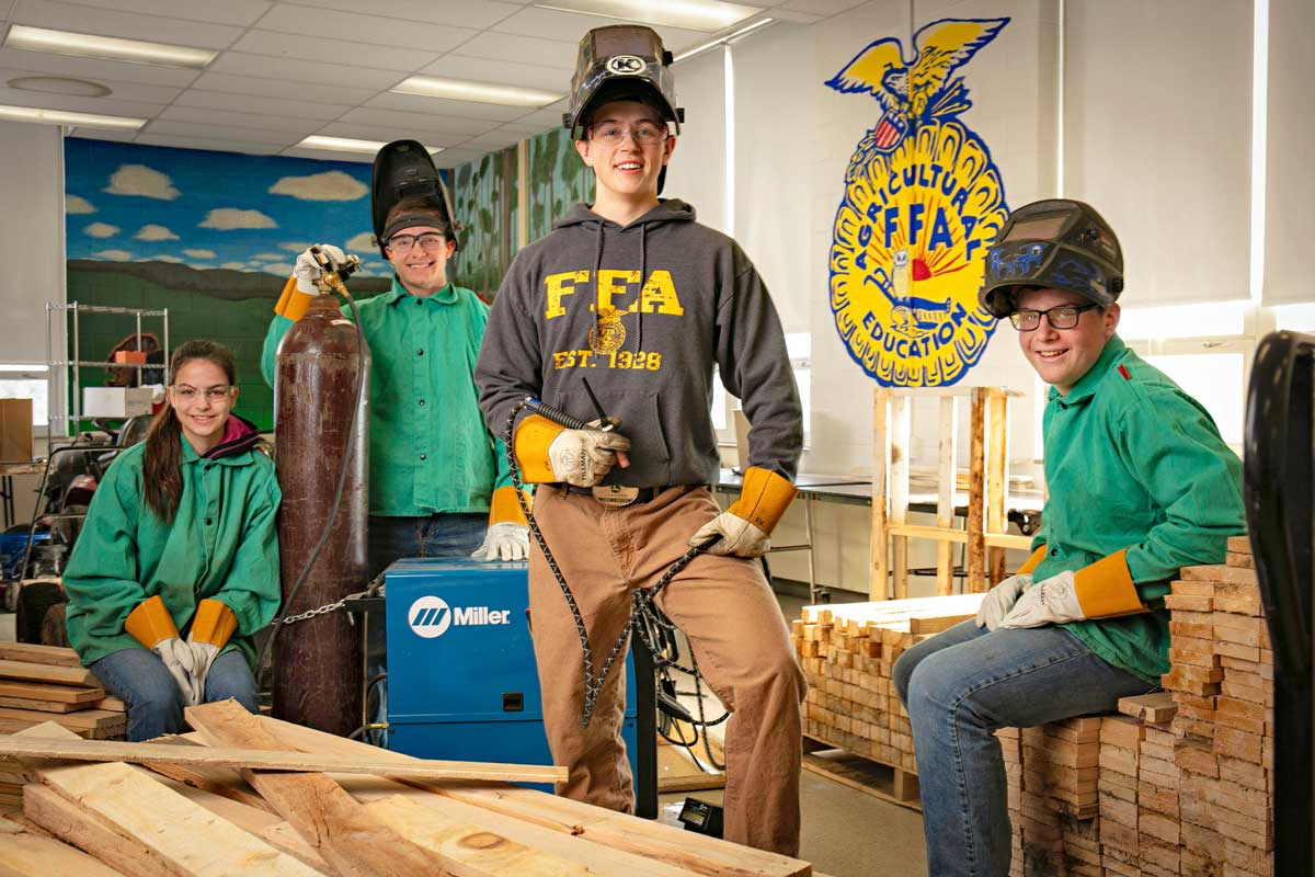 Photos of students posing with an elephant feeder they are building