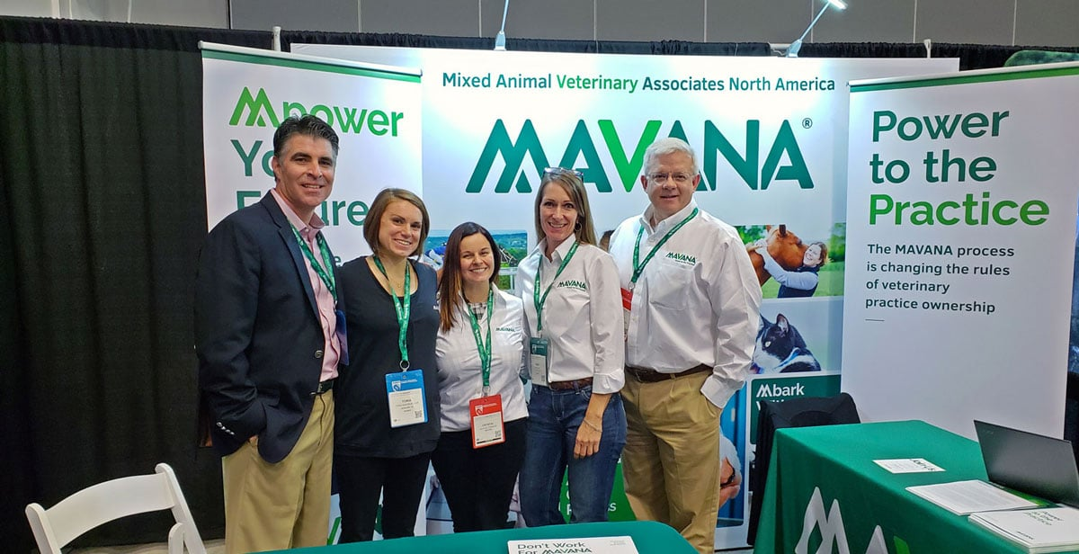 Group photo of MAVANA team members at a display booth.