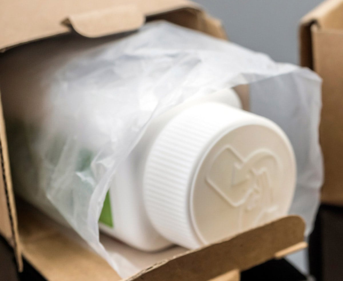 Photo of pill bottle in a box representative of a home delivery pharmacy.