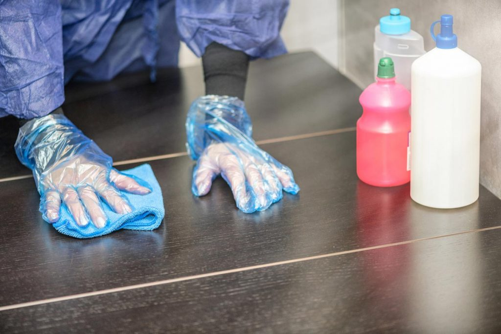 Photo of Veterinary professional in PPE cleaning a table representative of infection prevention