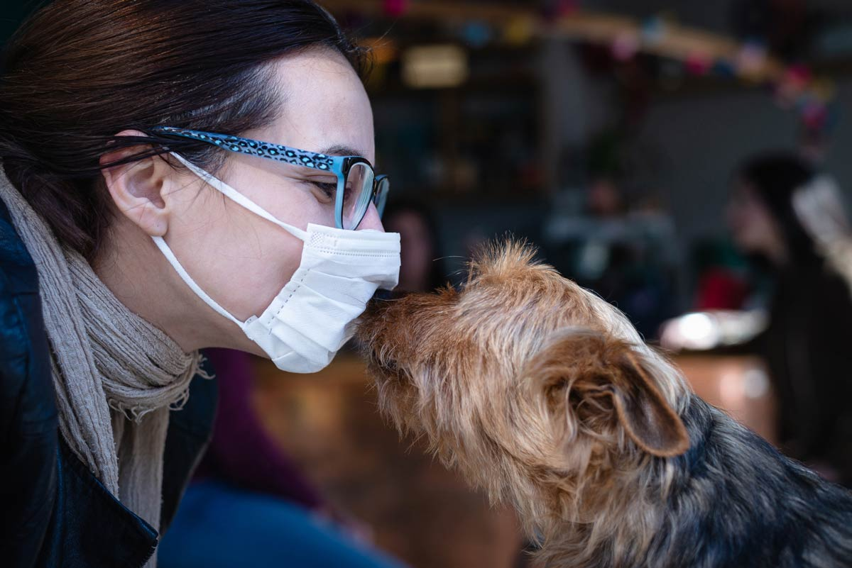 Photo of a dog owner wearing a mast and being nosed by their dog, representative of the human animal connection.
