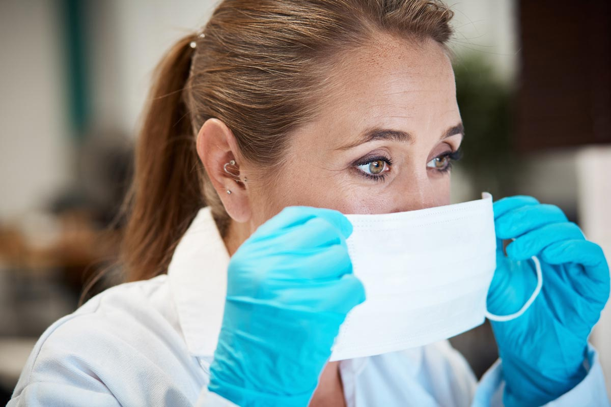 Photo of veterinarian putting on a mask with gloves representative of PPE.