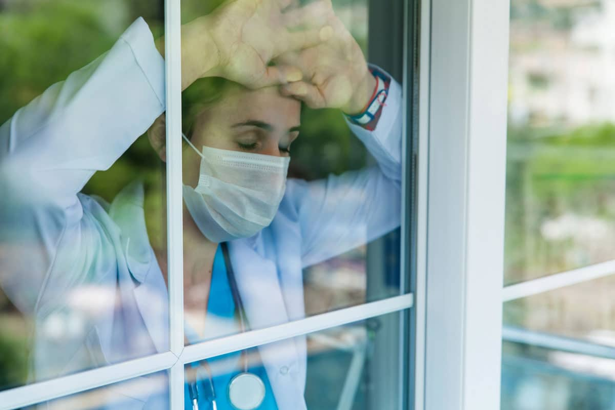 Photo of veterinarian with forehead against window pane representative of veterinary professional well-being.