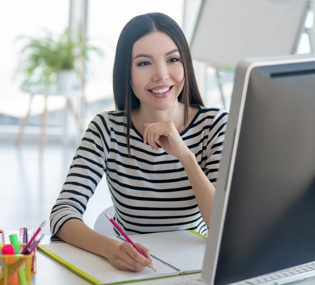 Photo of young woman at her computer representative of VMX 2021 online.