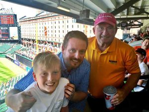 Photo of Paul Brennan with son and grandson at MLB game.