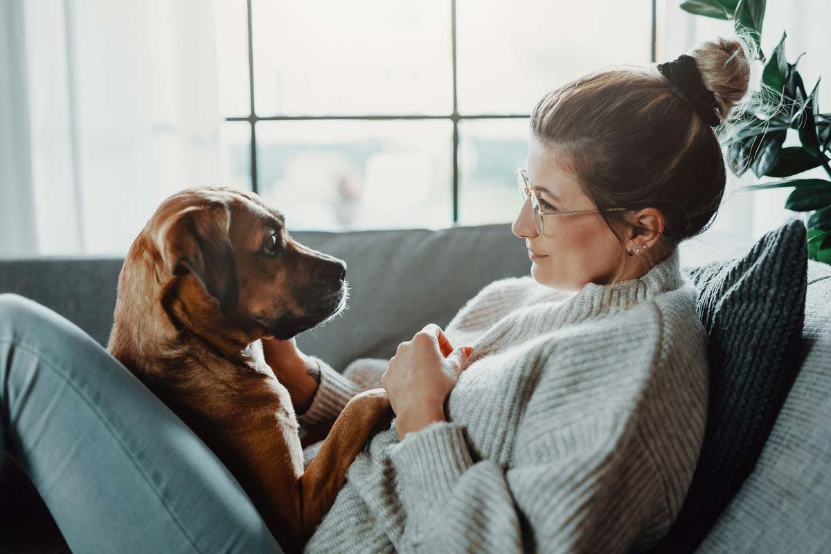 Photo of woman on couch with her dog representative of pet parenthood.