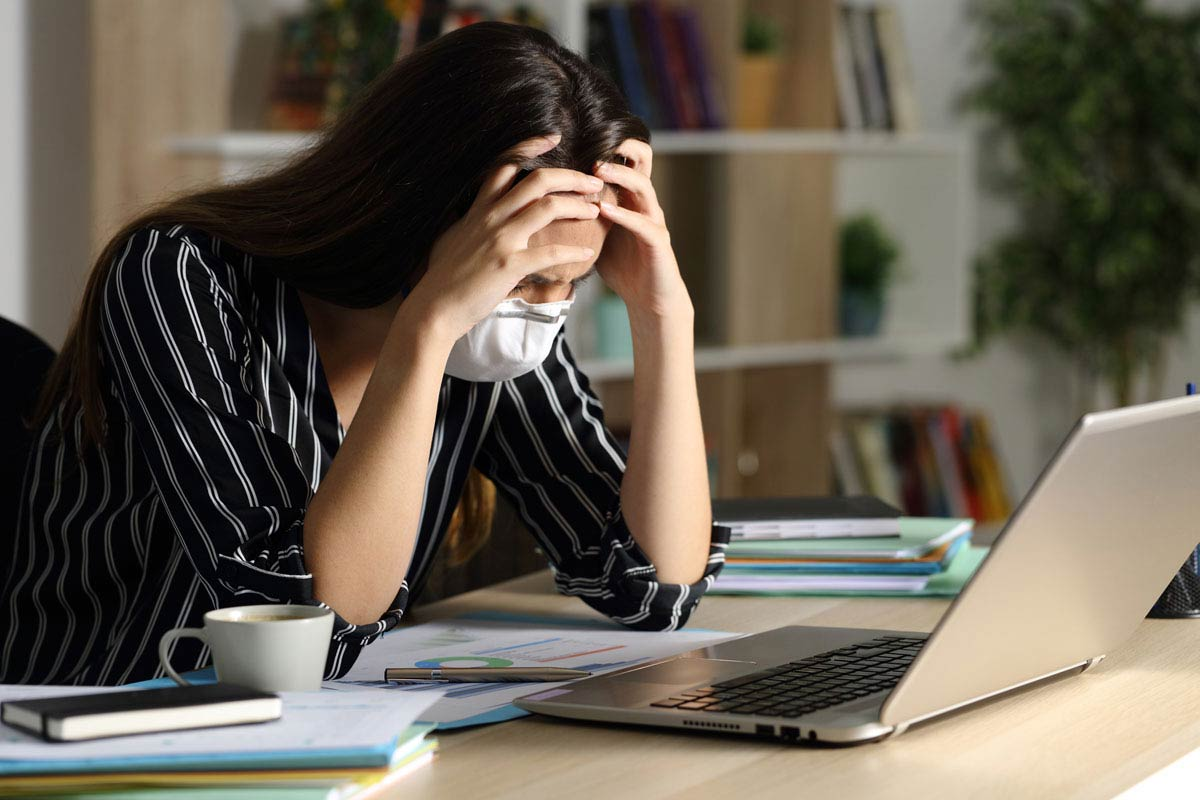 Photo of stressed young woman at her desk.