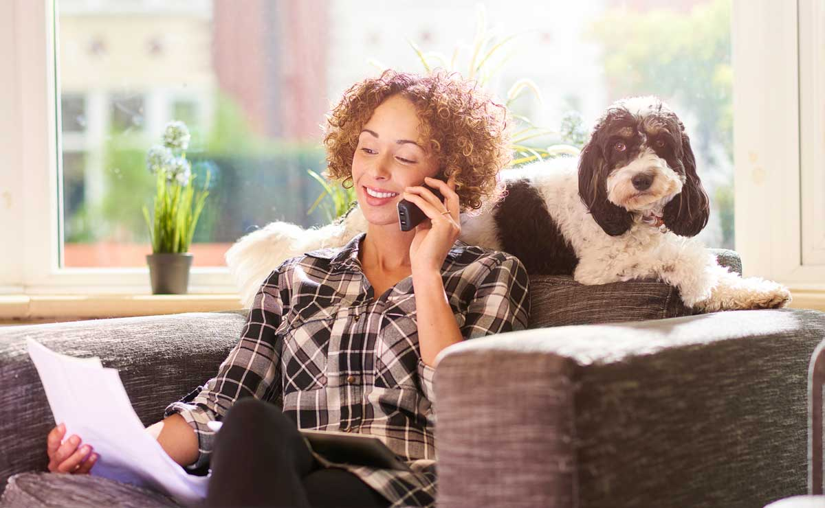 Photo of woman on phone with dog beside her representative of pet health insurance market.