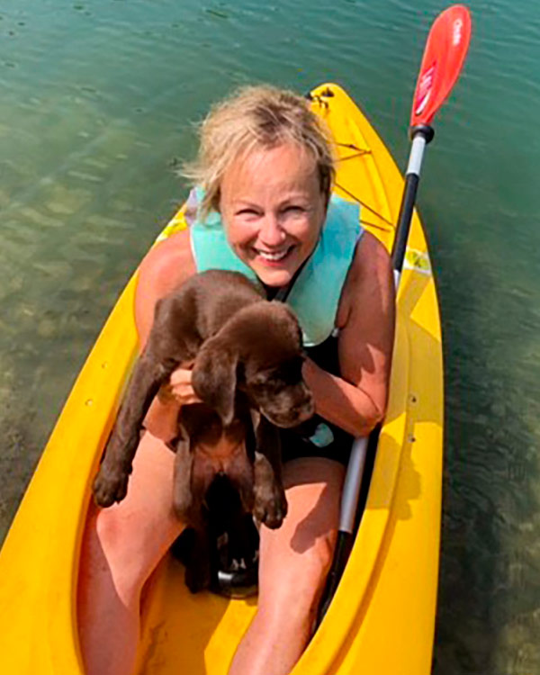 Photo of Janelle Brubaker and puppy in kayak.